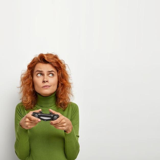 Donna energica attiva con espressione premurosa, utilizza la console di gioco per giocare ai videogiochi, indossa un maglione verde, guarda da parte, isolata sul muro bianco con uno spazio vuoto per la tua promozione. Foto Gratuite