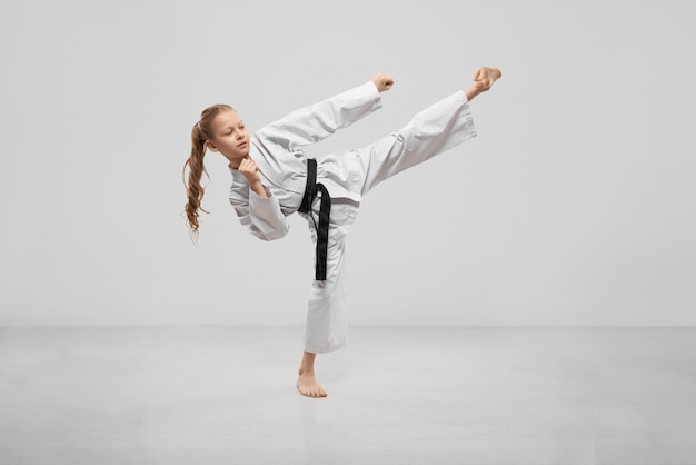 Active female teenager practising karate in studio Free Photo