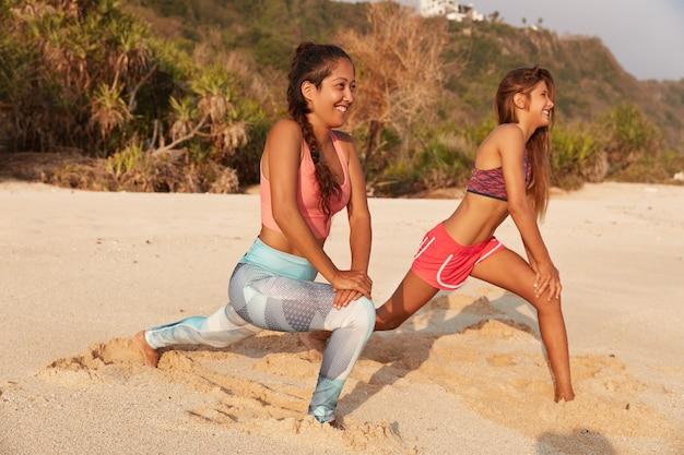 Le donne attive del fitness fanno affondi in spiaggia, allungano le gambe prima di correre, posano verso il mare sulla spiaggia sabbiosa Foto Gratuite