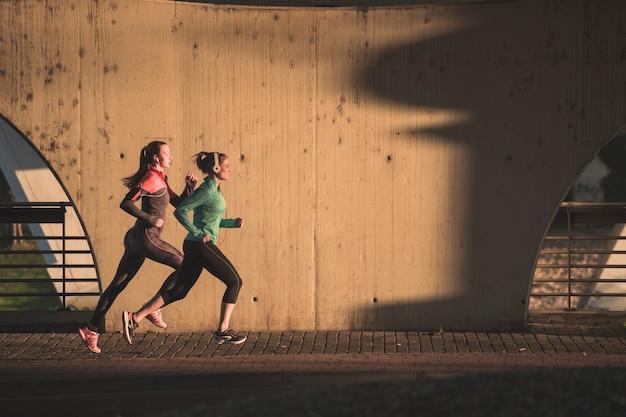 Активные девушки, работающие на закате Premium Фотографии
