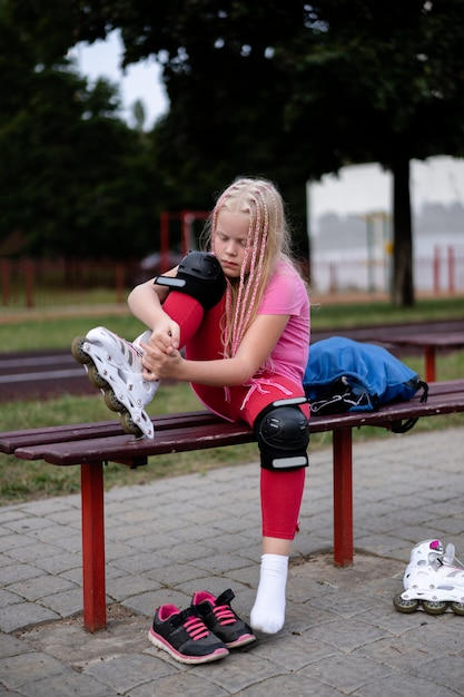 Active lifestyle in a modern city, girl puts on roller skates at the stadium Premium Photo