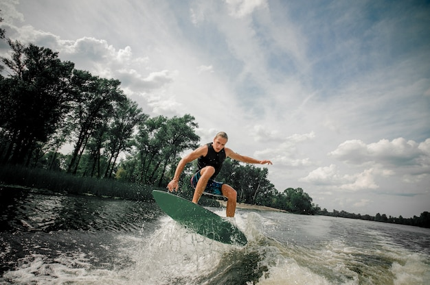 Active man wakesurfing on the board down the river Premium Photo
