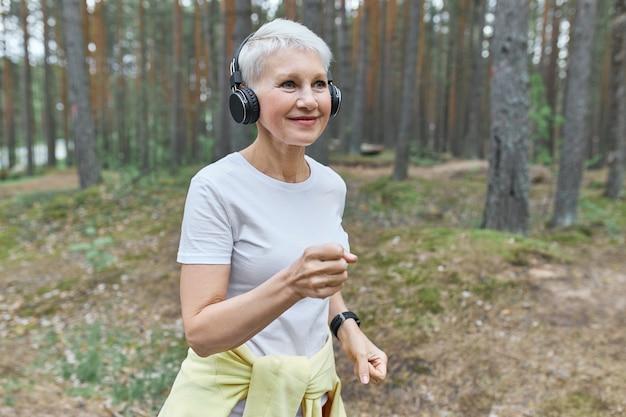 スポーツウェアとワイヤレスヘッドホンを着用し、ヘッドホンを着用して音楽を聴いているアクティブな成熟した女性ランナー。 無料写真