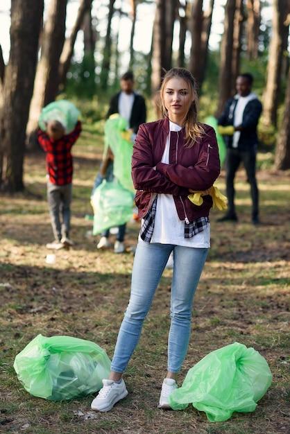 森でゴミ拾いをしている友達のボランティアを背景に、ゴミ袋がいっぱい入ったアクティブな可愛い女の子。 Premium写真