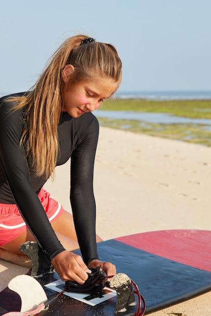 Активная девушка-профессионал, занимающаяся серфингом, одетая в купальники, с конским хвостом, фиксирует поводок, позирует на берегу Бесплатные Фотографии