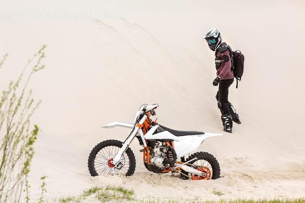 砂漠でバイクを見てアクティブなライダー 無料写真