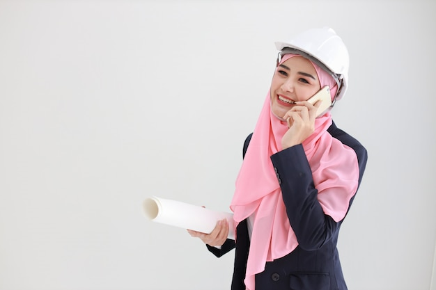Active and smart muslim young asian woman in blue suit smiling confident holding blueprint and using mobile phone Premium Photo