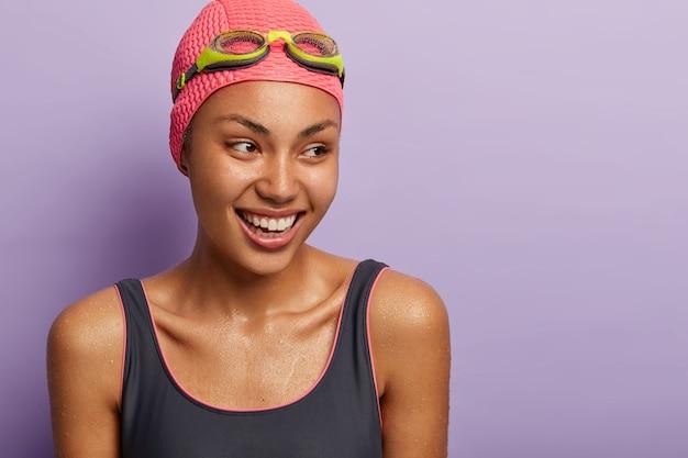 アクティブな笑顔の浅黒い肌の女性スイマーは、ダイビングの後に濡れ、水着、キャップ、ゴーグルを身に着け、脇に集中して、スポーティな体を持っています。レクリエーションと趣味 無料写真