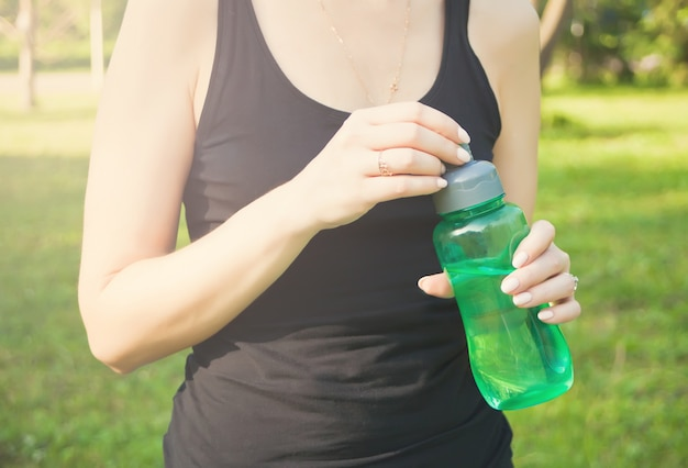 Active sporty woman holding bottle after training outdoors Premium Photo