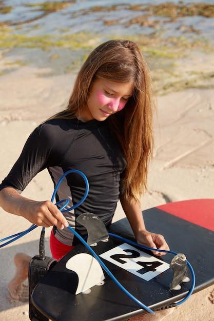 アクティブな夏休みのコンセプト。水着姿の魅力的な若い女性の屋外ショット、サーフボードの鎖を修正し、現在と戦う準備ができています 無料写真