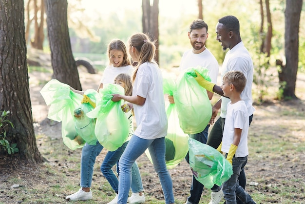 Активная команда международных любителей природы в белых футболках собирает мусор в полиэтиленовые пакеты в лесу. Premium Фотографии