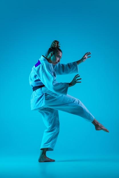 Активное обучение. профессиональная женщина-дзюдоистка в белом кимоно дзюдо практикует и тренирует, изолированные на синем неоновом фоне студии. Бесплатные Фотографии
