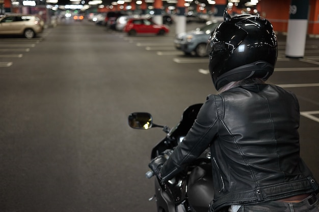 Active way of life, motorcycling, night city and people concept. rear shot of fashionable confident female biker wearing safety helmet and black leather jacket, riding her motorbike on parking lot Free Photo