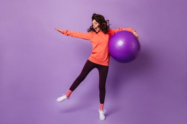 黒のレギンスと紫の壁にフィットボールでジャンプするオレンジ色のパーカーのアクティブな女性 無料写真