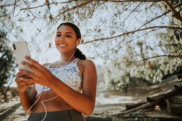 Active woman listening to music through earphones Premium Photo