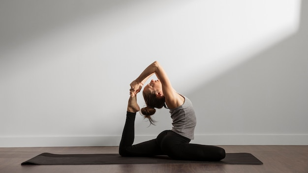 Active woman practicing yoga at home Free Photo