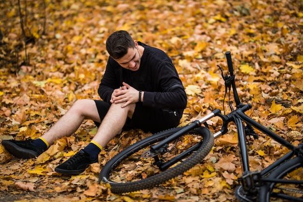 Активный молодой человек, держась за больную или сломанную ногу, лежа на дорожке в осеннем лесу на велосипеде Бесплатные Фотографии