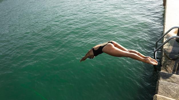 Giovane donna attiva che salta nell'acqua Foto Gratuite