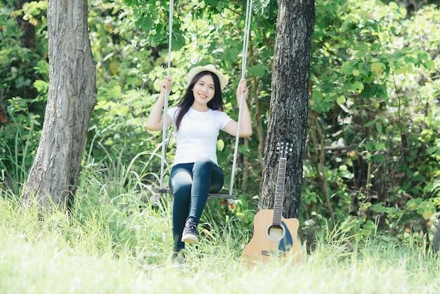 自然でacusticギターを持つ美しい若い女性 無料写真