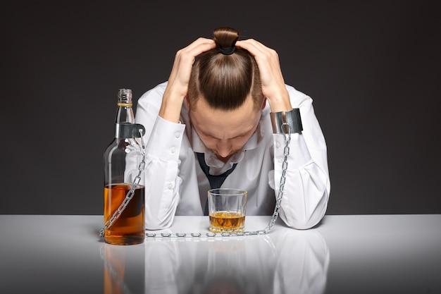 Addicted человек, глядя на свой стакан с виски Бесплатные Фотографии