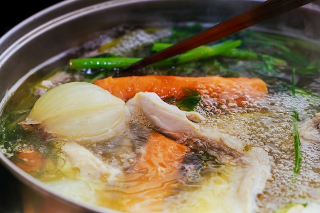 Adding chicken wings into saucepan. cooking chicken broth. Premium Photo