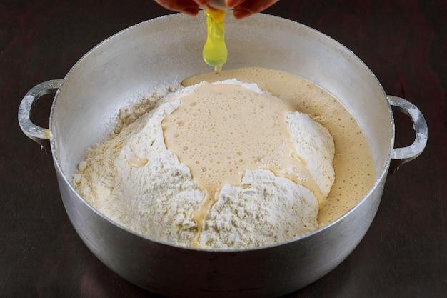 Добавляем яйцо в дрожжевое тесто для приготовления булочек Premium Фотографии