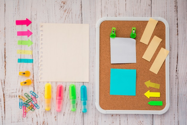 Adhesive notes on cork board with blank notepaper; highlighter and paper clips over wooden backdrop Free Photo
