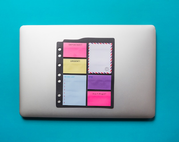 Adhesive notes with envelope stucked on laptop against blue background Free Photo