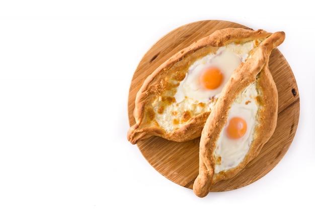 チーズと卵を白で隔離される伝統的なadjarianグルジアkhachapuri。上面図。 Premium写真