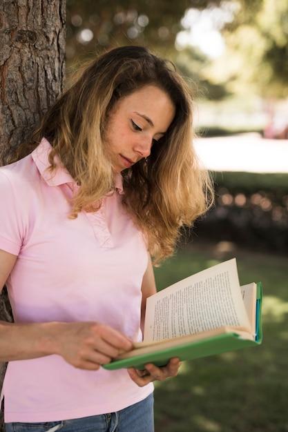 Подросток женского чтения учебник в парке Бесплатные Фотографии
