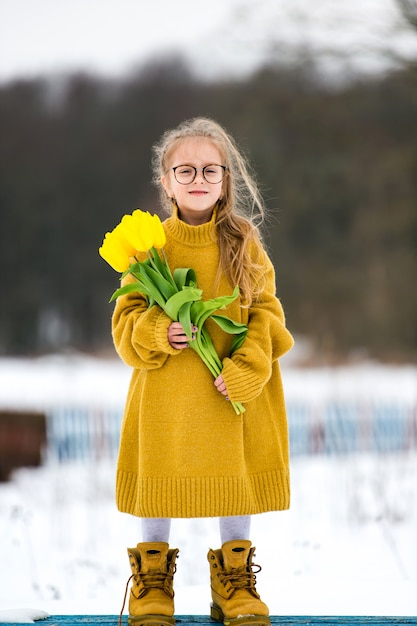 Adorabe little girl wearing adult oversized sweater and big fathers boots. beautiful young  girl in glasses standing on bench with bouquet of yellow tulips in snowy winter day. Premium Photo