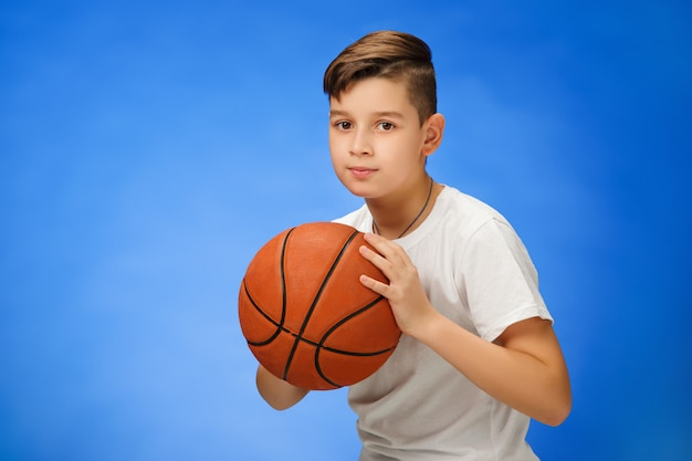 Adorable 11 year old boy child with basketball ball Free Photo