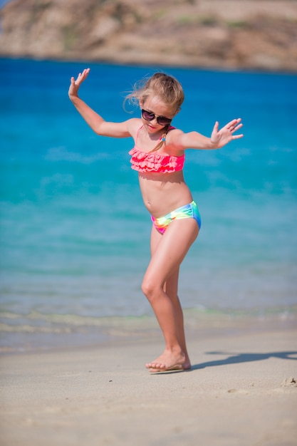 Adorable active little girl at beach during summer vacation Premium Photo
