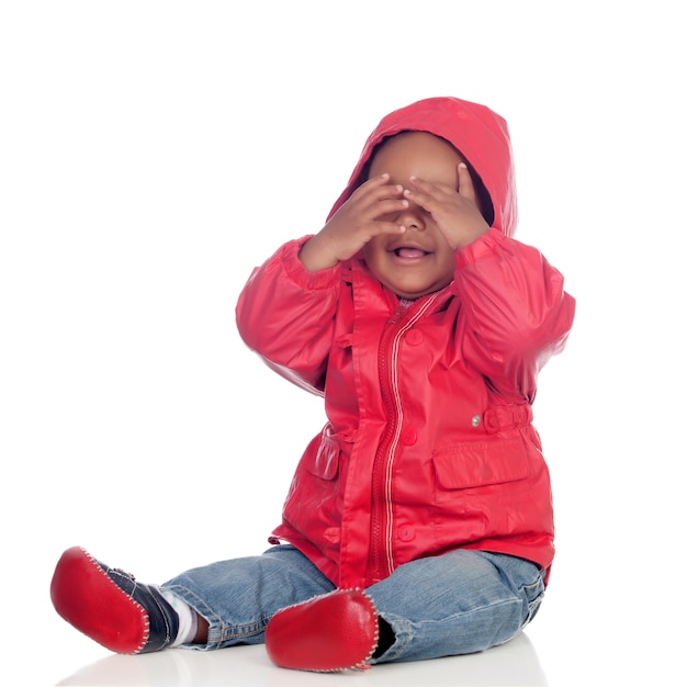 Adorable african baby sitting on the floor with red raincoat covering the face Premium Photo