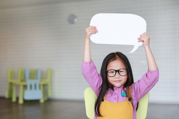 Adorable asian little girl holding empty blank speech bubble to say something in the classroom with smiling and looking straight at camera. education and conversation concept. Premium Photo