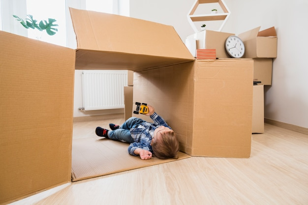 Adorable baby boy lying in the cardboard box playing with toy car at home Free Photo