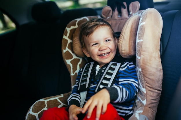 Adorable baby boy in safety car seat. Premium Photo
