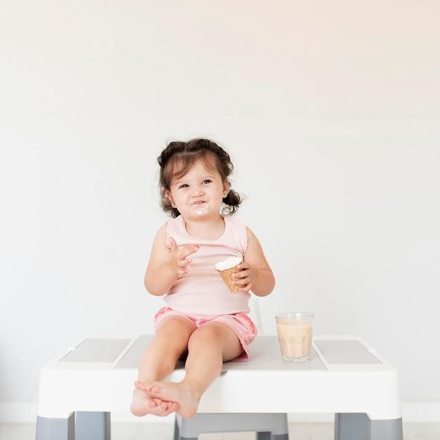 Adorable baby girl eating ice creem Free Photo