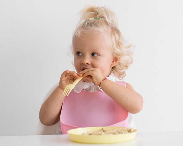 Adorable baby playing with food Premium Photo