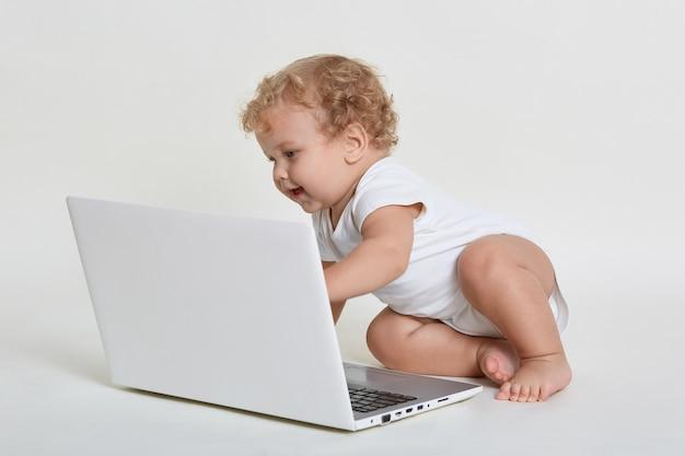바닥에 앉아 종료 된 표정으로 노트북 화면을보고 사랑스러운 아기 프리미엄 사진