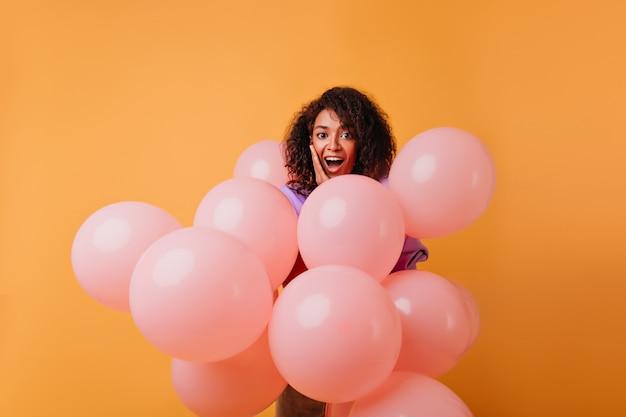 미소로 파티를 즐기는 사랑스러운 흑인 여성. 오렌지에 서있는 핑크 헬륨 풍선과 함께 매혹적인 여성 모델. 무료 사진