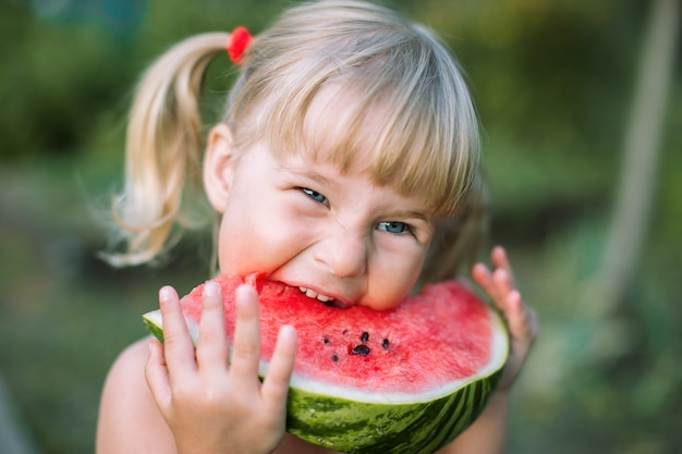 Adorable blonde girl eats a slice of watermelon outdoors Premium Photo