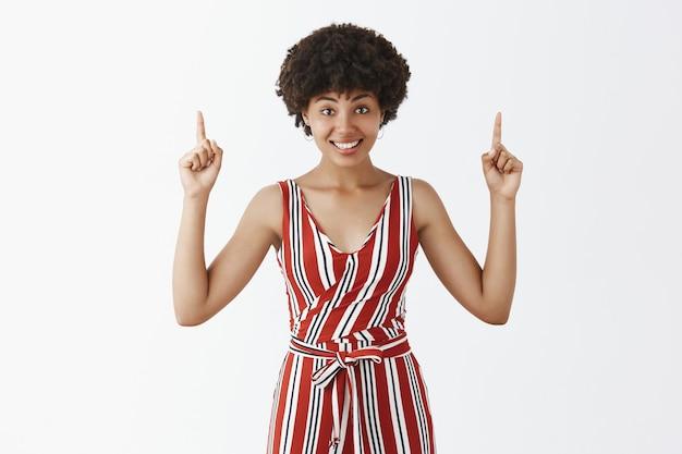 愛らしい屈託のない、幸せなアフリカ系アメリカ人の巻き毛のヘアスタイルを上げられた人差し指で上向きにし、コピースペースに最適な場所を提供しながら楽しく笑顔 無料写真