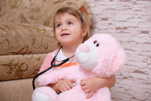 Adorable child playing doctor or nurse with plush toys at home. Premium Photo
