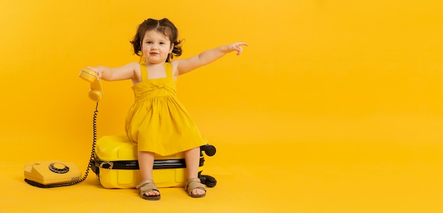 Adorable child posing with telephone and luggage Free Photo
