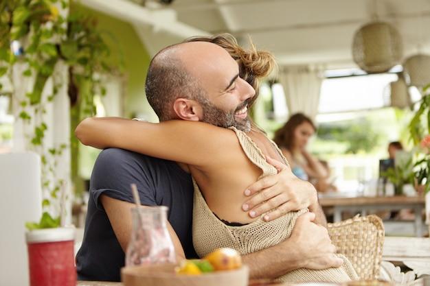 愛らしいカップルが一緒にいることを楽しんで、お互いを優しく抱き締めます。ひげを生やした彼氏を抱きしめ、仕事での昇進を祝福するスタイリッシュな女性。 無料写真