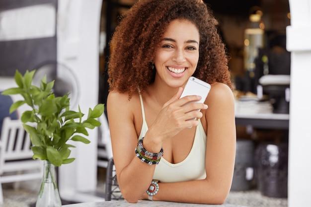 肯定的な表情の愛らしい巻き毛の女性は、携帯電話を手に持ち、ソーシャルネットワークにメッセージを持ち、カフェテリアで高速インターネット接続を楽しんでいます。 無料写真