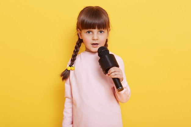 Adorable cute child with microphone in hands singing songs, looks at camera, performing isolated over yellow background, child arranging concert, sings in karaoke. Free Photo