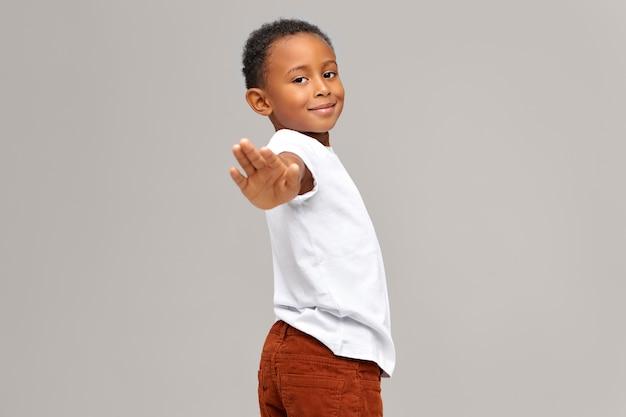 Очаровательный милый темнокожий мальчик протягивает руку, делая стоп-жест или прощаясь. красивый афро-американский ребенок мужского пола жесты, давая знак, отправляя сообщение. невербальная коммуникация Бесплатные Фотографии