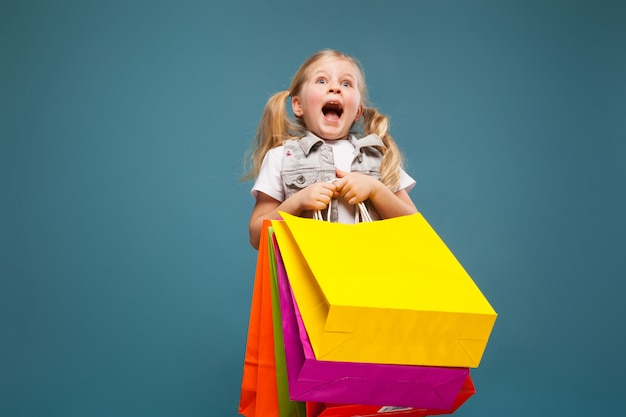 Adorable cute little girl in white shirt, white jacket and white shorts hold colorful paper bags Premium Photo